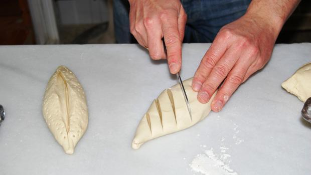 Un panadero da unos cortes a una pieza de masa