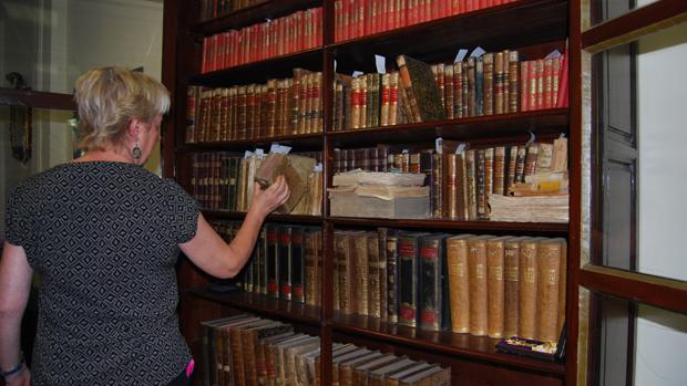 Una mujer consulta una de las joyas bibliográficas de Dos Hermanas