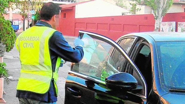 Un agente de la Guardia Civil inspecciona un vehículo