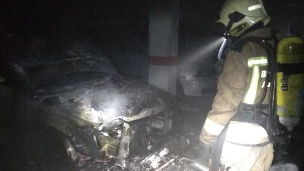 Un bombero del parque de Santiponce en el interior del garaje tras apagar el incendio del coche