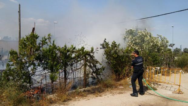 Un policía local de Coria apaga un fuego con la manguera de un particular ante la ausencia de los bomberos
