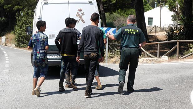 Un guardia civil acompaña a un grupo de menores extranjeros que se había escapado en Barbate