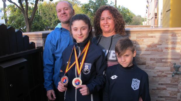 Lucía Elías muestra las medallas ganadas en Cáceres, acompañada de su familia