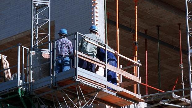 Unos obreros encima del andamio de un edificio