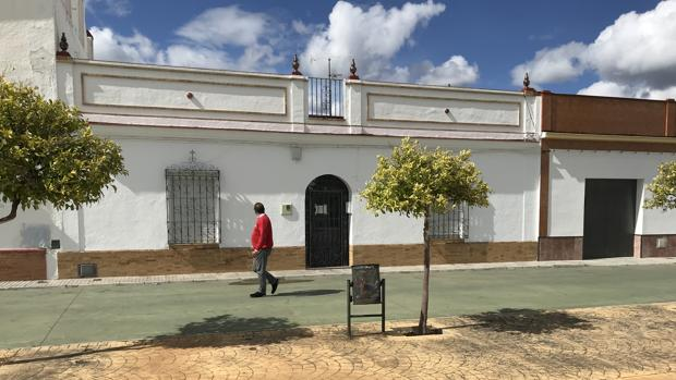 Un vecino pasea por delante de la vivienda donde fue hallada muerta Floriana, en Aznalcóllar