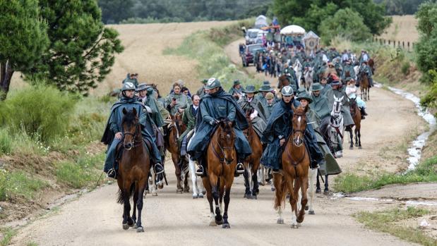 Tres guardias civiles a caballo abren paso al Simpecado de la Matriz de Almonte en la lluviosa Romería de 2016