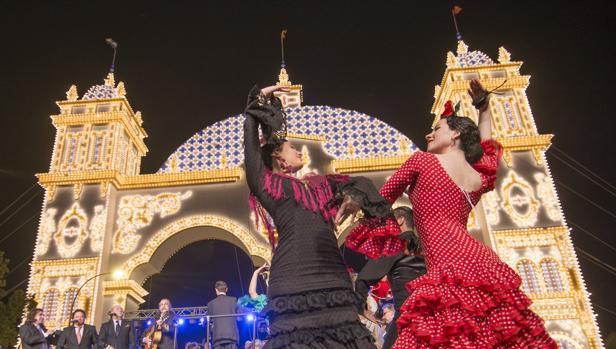 Dos flamencas bailan frente a la portada de la Feria de Abril de Sevilla