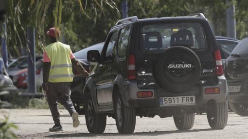 Un aparcacoches africano acompaña al vehículo