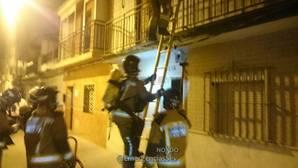 Efectivos del cuerpo de bomberos escalando para acceder a la vivienda afectada por la explosión