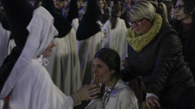 Una nazarena de la Macarena llora tras la primera avalancha