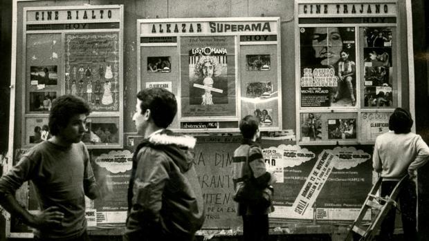 Varios jóvenes consultan carteleras en una imagen de 1978