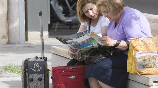 Dos visitantes consultan un mapa de la ciudad en un banco