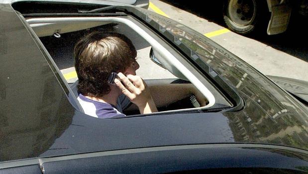 Un joven habla por el móvil en el interior de su vehículo