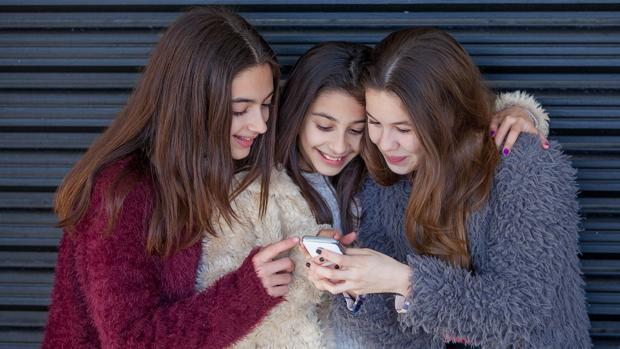 Un grupo de niñas mira el móvil