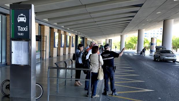 Varias personas esperan a un taxi mientras son atendidas por un Policía