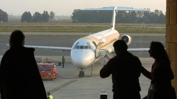 Pasajeros en la puerta de embarque contemplan la llegada de un avión