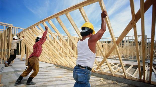 Varios obreros levantan una estructura de madera