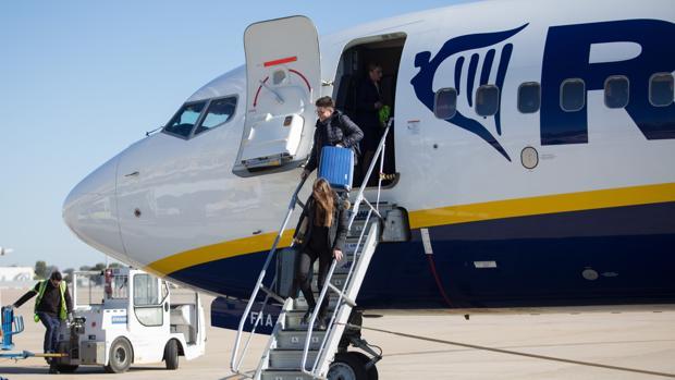 Dos pasajeros bajan de un avión en el aeropuerto de Sevilla