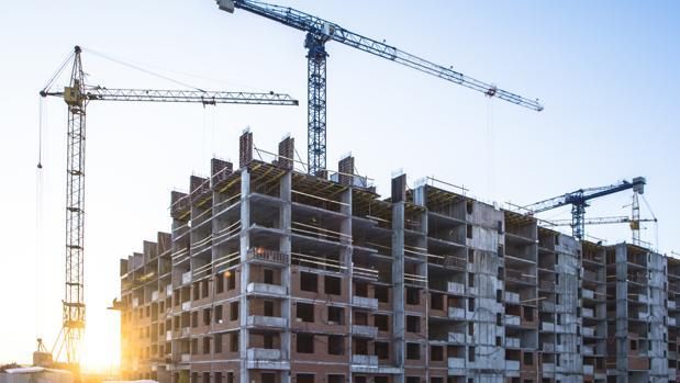 Un edificio en obras rodeado de grúas