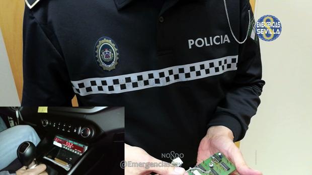 Un agente enseña la placa del taxímetros