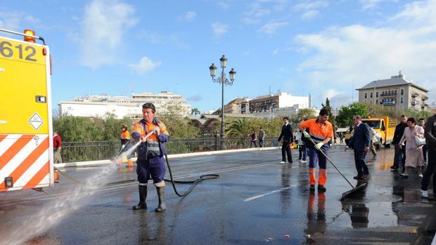 Operarios de Lipasam limpiando en el puente de Triana tras el paso de cofradías