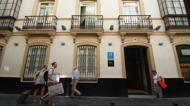 Varios visitantes en la entrada de un céntrico hotel de Sevilla