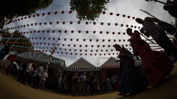 Flamencas pasando bajo un cielo de farolillos en la Feria este viernes
