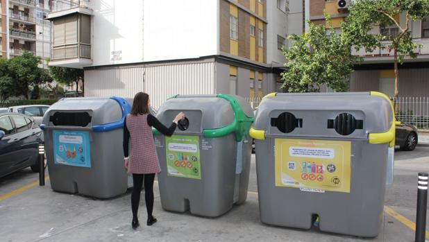 Una joven deposita una botella de vidrio en un contenedor verde de Lipasam