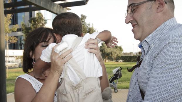 Una pareja sevillana coge en brazos al niño que adoptaron