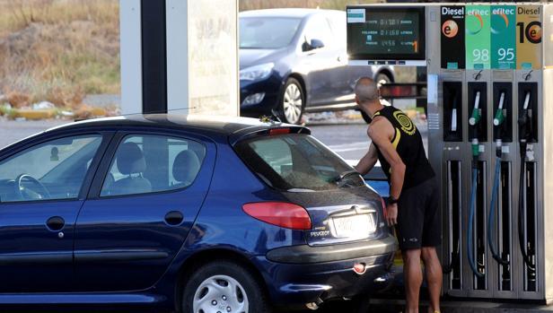 Un cliente se sirve gasolina en un surtidor de una gasolinera de Sevilla.