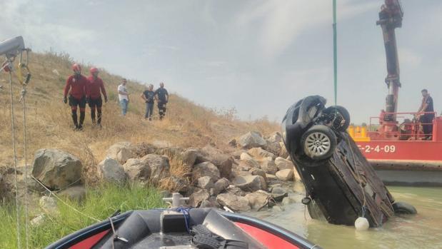 Los bomberos trabajan en sacar el vehículo del río