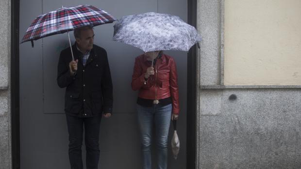 Una pareja de viandantes se protege de la lluvia con unos paraguas