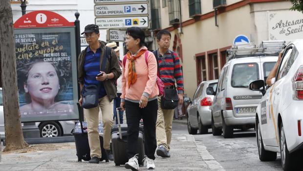 Varios turistas tiran de sus maletas por una de las calles de Sevilla