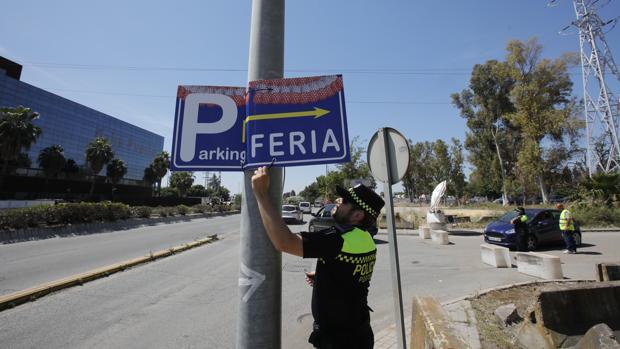 Un agente retira un cartel que dirigía a los conductores a uno de los aparcamientos ilegales