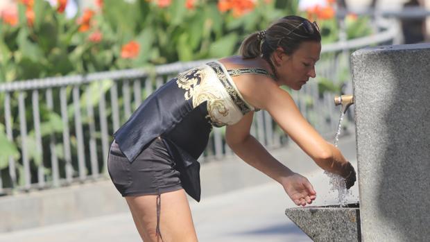 Una mujer se refresca en una fuente de Sevilla