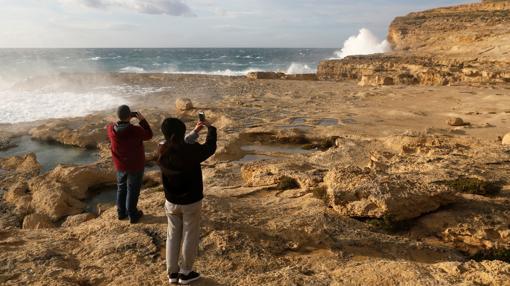 Dos personas fotografían la zona donde estaba la Ventana Azul