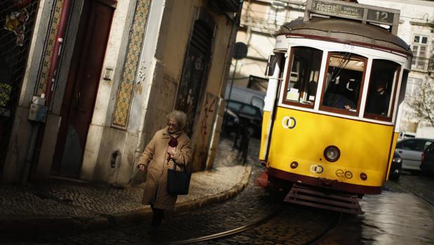 Una mujer pasea por el barrio de la Alfama, junto a uno de los típicos tranvías de Lisboa