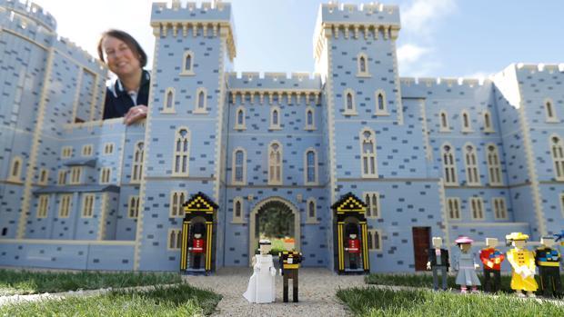 La diseñadora de esta atracción Paula Laughton posa junto al Castillo de Windsor y los novios construidos con bloques de Lego